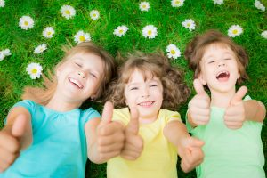 35407522 - happy children lying on green grass in spring park. laughing kids showing thumbs up